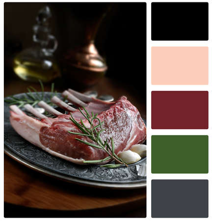 Rack of lamb ready to be prepared for cooking with rosemary. Selective focus. Copy space with complimentary colour swatch included. Stock Photo