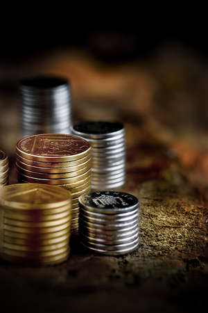 brown background: Creatively lit stacked gold and silver coins against a rustic background with generous accommodation for copy space. The perfect image for your financial document cover design. Selective focus.