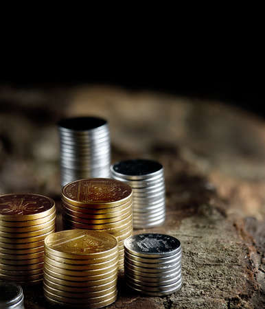 accommodation space: Creatively lit stacked gold and silver coins against a rustic background with generous accommodation for copy space. The perfect image for your financial document cover design. Selective focus.