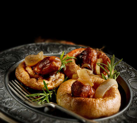 Classic English pub food dish of Yorkshire Pudding with pork sausages served with red wine onion gravy with a rosemary herb garnish. Perfect image for your bistro menu cover design. Copy space.