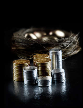 Creatively lit pension concept image with stacked currency and golden eggs in a nest in the dark background. Generous accommodation for copy space.