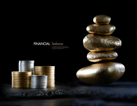 feng: Financial concept image representing investment balance. Gold and silver currency coins with stacked stones against black with generous accommodation for copy space.