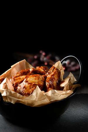 lit image: Creatively lit marinated chicken pieces with BBQ sauce prepared for cooking. The perfect image for your restaurant or bistro cover design. Generous accommodation for copy space.