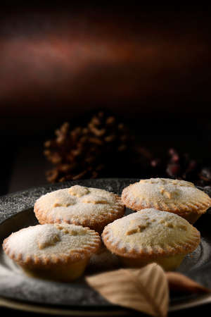 Festive luxury all butter mince pies, a traditional British Christmas dessert, creatively lit against a rustic background. Generous accommodation for copy space.