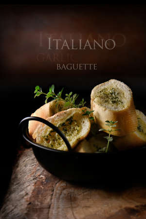 baton: Fresh Italian garlic sliced baguette bread roll ready for serving against a rustic background seasoned with fresh thyme herbs. The perfect image for your rustic menu cover design art. Copy space.
