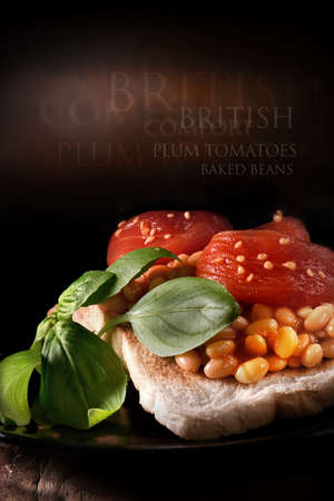 beans on toast: Ripe plum tomatoes with baked beans on toast with basil herbs against a rustic background with generous accommodation for copy space. Stock Photo