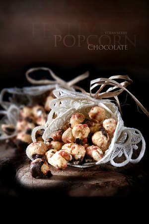 Creatively lit chocolate and strawberry festive popcorn against a rustic setting. Generous accommodation for copy space. Stock Photo
