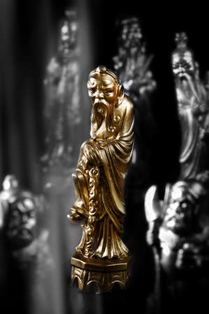 Chinese Emperor antique chess piece in gold against a dark background. Concept image for strategy, intelligence, success and competition. Selective focus and composition.