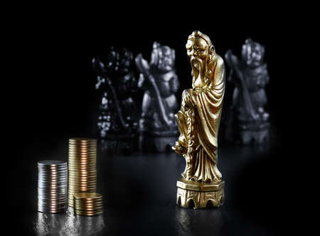 Antique Chinese chess piece with generic currency coins against a dark background. Concept image for strategy, intelligence, success and competition. Copy space.
