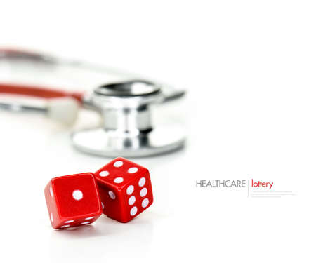 depending: Two red dice and stethoscope close-up against a light background with copy space. Concept image for postcode lottery healthcare, receiving better health care depending where you live.
