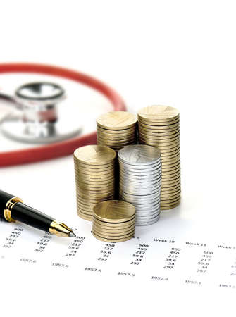 Stethoscope, stacked coins, spread sheet and a pen against a light background with copy space. Concept image for soaring social care costs in the community.