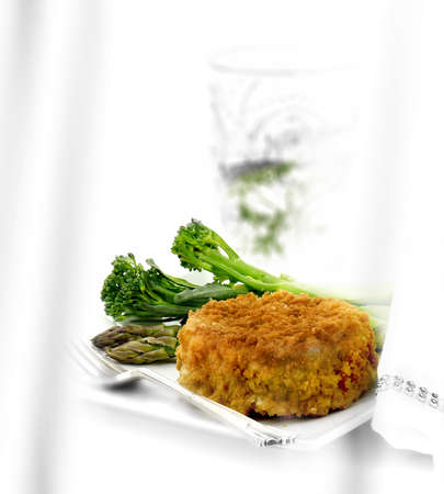Classic cod fish cake with seasonal vegetables of broccoli stems and asparagus shoots. Shot against a white background with generous accommodation for copy space.