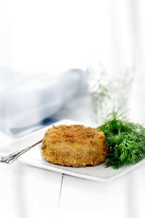 Classic cod fish cake with dill herb. Shot against a white background with generous accommodation for copy space.