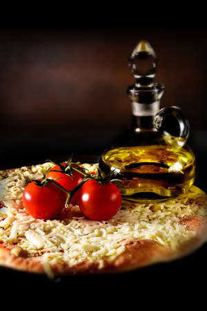 grated mozzarella cheese: Classic Italian margherita pizza smothered with grated mozzarella cheese and tomato sauce shot against a rustic background with creative lighting. the perfect image for your take-away menu or bistro menu cover art.