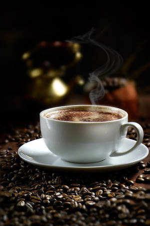 Dark, creatively lit steaming Italian Cappuccino coffee in a stylish, modern, white ceramic cup on a bed of fresh coffee beans. Generous accommodation for copy space.