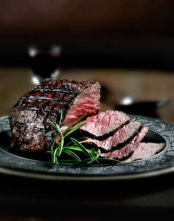 Creatively lit, fresh British roast beef sliced for serving against a dark background with rosemary herb garnish. Generous accommodation for copy space. Stock Photo