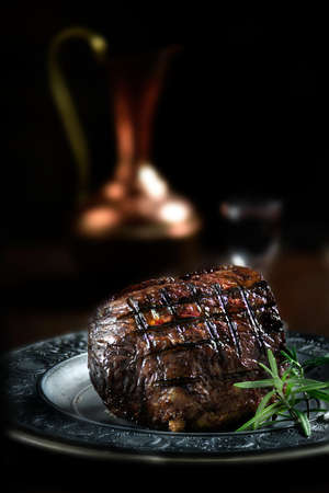 Creatively lit, fresh British roast beef resting for carving against a dark background with rosemary herb garnish. Generous accommodation for copy space.