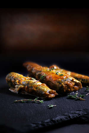 Mediterranean sardines in a rich tomato sauce with thyme herbs shot in creative light against a dark, rustic background with generous accommodation for copy space.