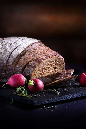 traditionary: Leavened rustic Rye loaf shot against a dark background with fresh radish with generous accommodation for copy space.