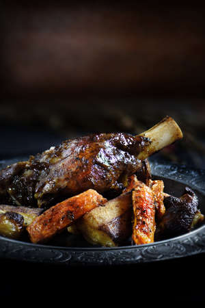 Roasted lamb shank with root vegetables of parsnip, carrots and shallots. Selective focus with generous accommodation for copy space.