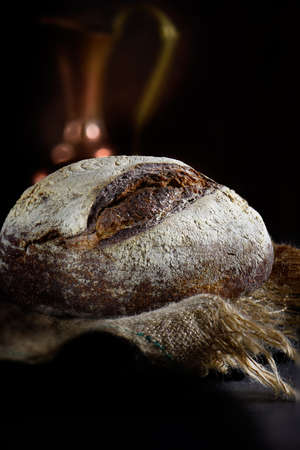 Tradiitonal French stone baked Levian Rye Boule loaf with wheat, wholegrain rye and barley flour shot against a dark rustic backround with generous accommodation for copy space. Stock Photo