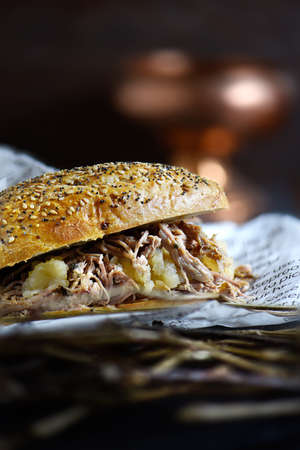 Rustic pulled roast pork sandwich with apple sauce against a dark background with generous accommodation for copy space.