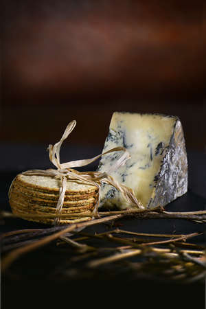 tabla de quesos: Rustic styled image of mature English Blue Stilton cheese with stacked Scottish oatcakes wrapped in raffia against a dark background with generous accommodation for copy space. Foto de archivo