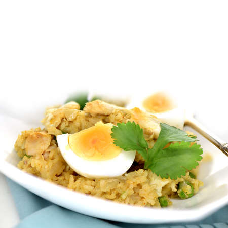 flaked: Kedgeree with flaked smoked haddock, basmati rice, peas, onions, halved boiled eggs and cilantro garnish against a white background with generous accommodation for copy space.