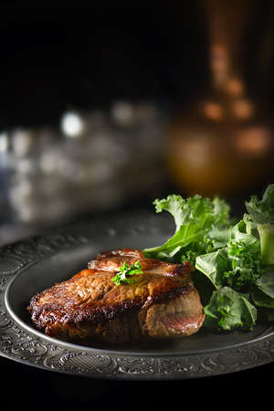 Creatively lit differential focus, rump steak with kale leaves shot against a dark, rustic background with generous accommodation for copy space. Perfect image for your restaurant or bistro cover art. Stock Photo