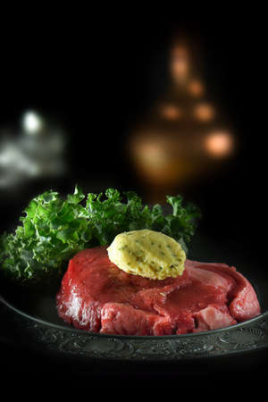 Creatively lit uncooked rump steak with chilled mustard butter garnish set against a dark background with generous accommodation for copy space. Concept image for cooking preparation and dining.