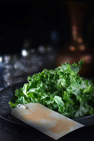 Fresh organic kale (Brassica oleracea) shot in creative dark lighting with generous accommodation for copy space. Label for your own overlay text if needed. Rustic concept image for healthy eating.