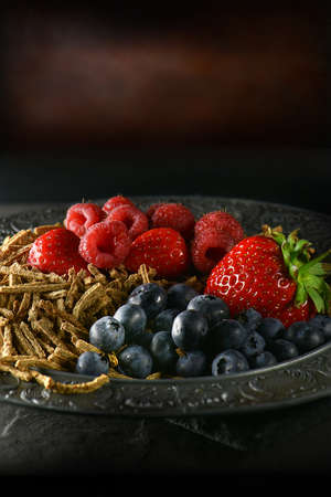Bran flakes with fresh soft fruits with creative lighting against a dark rustic background. Generous accommodation for copy space. Concept image for healthy eating. Stock Photo