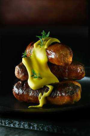 A real hotdog. Stacked grilled pork sausages smothered with English mustard. Concept food art image for bistro or restaurant menu cover art. Generous accommodation for copy space. Stock Photo