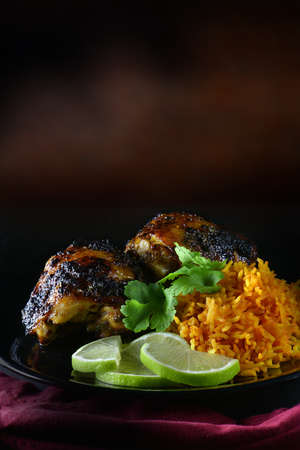 Grilled chicken thighs in marinade of lime juice, coriander leaves and brown sugar, cumin and crushed garlic cloves. Creatively lit with generous accommodation for copy space. Stock Photo