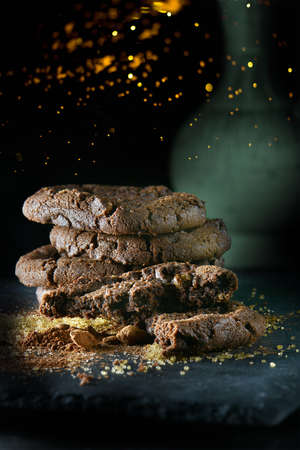 Christmas themed triple chocolate chip cookies stacked with scattered sugar and cocoa on a slate base. Shot against a dark, rustic background with glitter and generous accommodation for copy space.