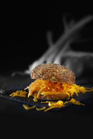 Organic granary, seeded bread roll with grated red cheese, commonly known as Red Leicester, shot against a dark background with creative lighting. Generous accommodation for copy space.