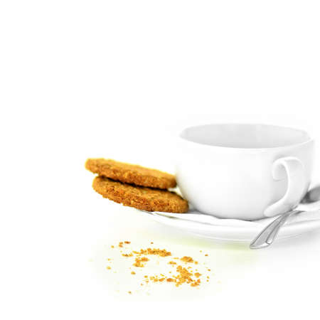 Concept image for mediation or business meeting, interview etc. Crumbly biscuits and a stylish, modern cup, saucer and spoon against a white background. Copy space. Stock Photo