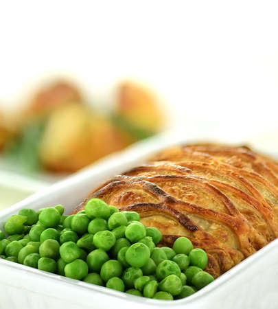Salmon en croute with lattice filo pastry with fresh garden peas and roasted potatoes shot against a white background with copy space.