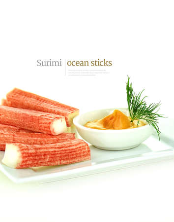 Fresh surimi ocean sticks, also referred to as crab or seafood sticks, shot against a white background with a dill herb garnish. Copy space.