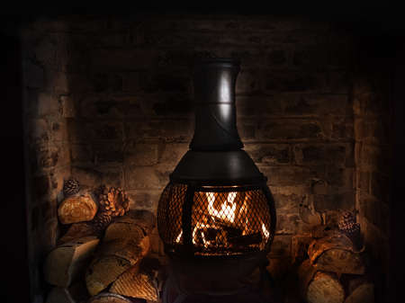 Cast iron wood burner in old brick fireplace burning chopped wood, Concept image for Christmas, winter, Thanksgiving, stockings, festive, restaurants, bistros, eateries etc.