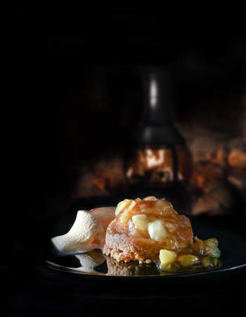 Bramley apple crumble dessert served with vanilla ice cream against a rustic, dark, cozy background with generous accommodation for copy space. Stock Photo
