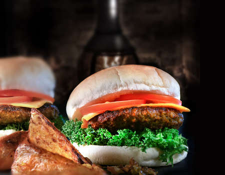 generosa: Rustic styled image of two fresh beef burger with spicy potato wedges, tomato, melted cheese and fried onions against a dark homey background with generous accommodation for copy space.