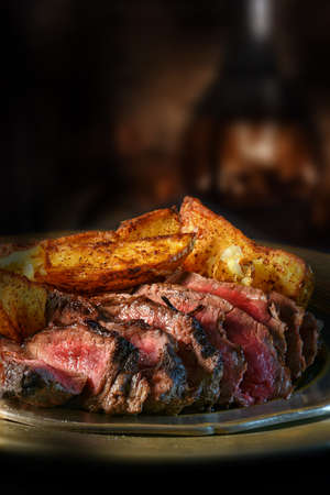 Rustic setting sliced rump steak served with spicy potato wedges against a dark background. The erfect image for your bistro menu cover art. Copy space. Stock Photo