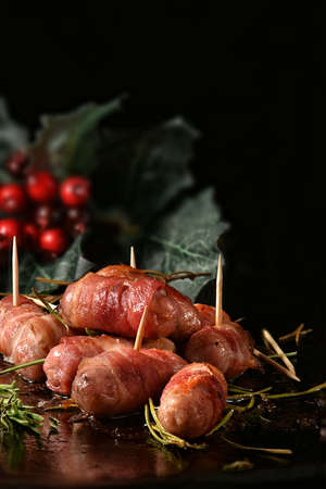Festive cocktail sausages wrapped in crispy smoked bacon commonly known as 'Pigs in Blankets' shot against a festive dark background with creative lighting with generous accommodation for copy space.