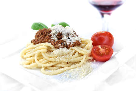 Classic Italian Spaghetti Bolognese with grated parmesan cheese and fresh tomatoes shot against a light background with differential focus. Copy space.