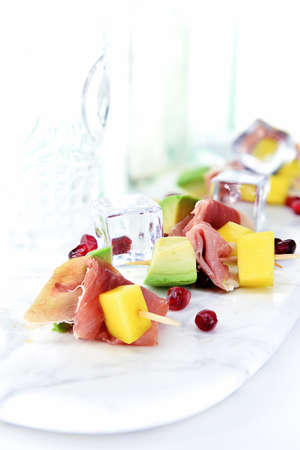 Chilled with ice cubes, fresh avocado, melon, pomegranate and Italian ham Prosciutto appetizers shot against a light background. Generous acommodation for copy space. Stock Photo