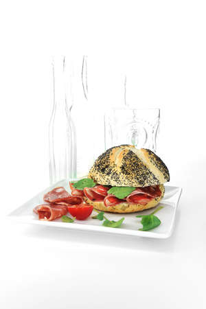 Salami and watercress sandwich in a poppy-seed bread roll shot against a white background with generous accommodation for copy space.