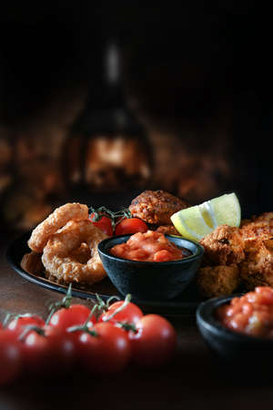 Creatively lit vegetarian Tex-Mex platter with spicy potato wedges, garlic mushrooms, onion rings and sweetcorn & jalapeno fritters and salsa dip shot against a dark, rustic background. Copy space.