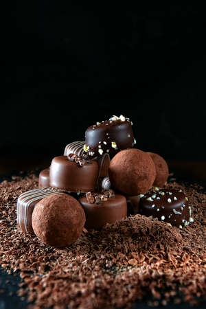 Handmade dark milk chocolates set against a dark rustic background with differential focus and generous accommodation for copy space. Stock Photo