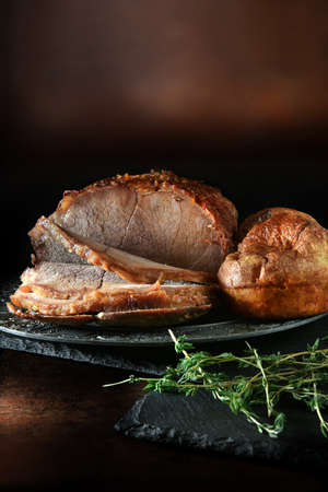 Classic British roast beef joint, slow roasted and carved with traditional English Yorkshire Puddings shot against a rustic dark background with generous accommodation for copy space.